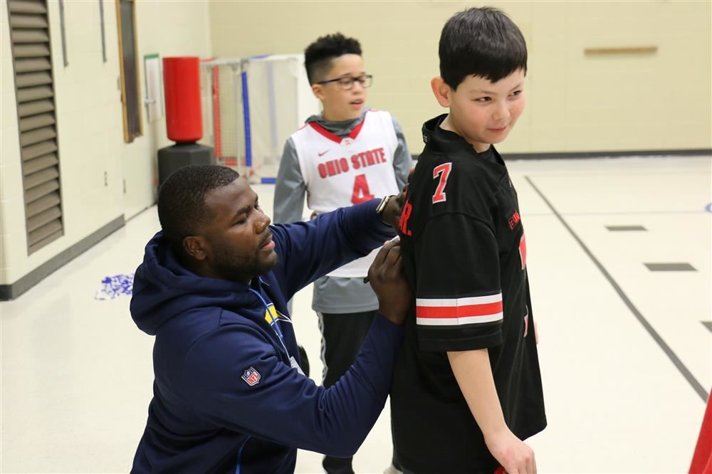 Cardale Jones signs a jersey during a school visit